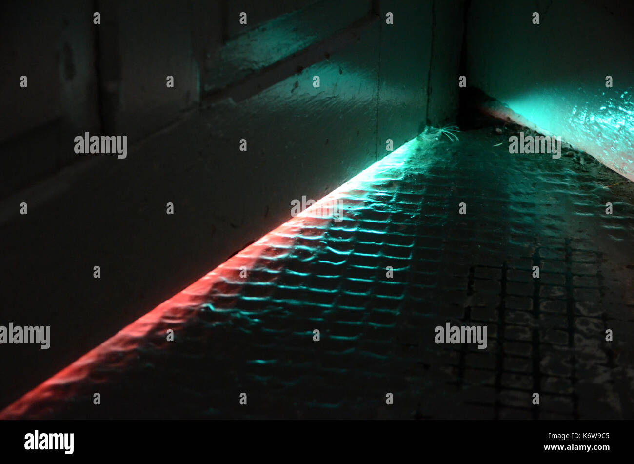 Light in strange colors seen coming from under a door. - Stock Image