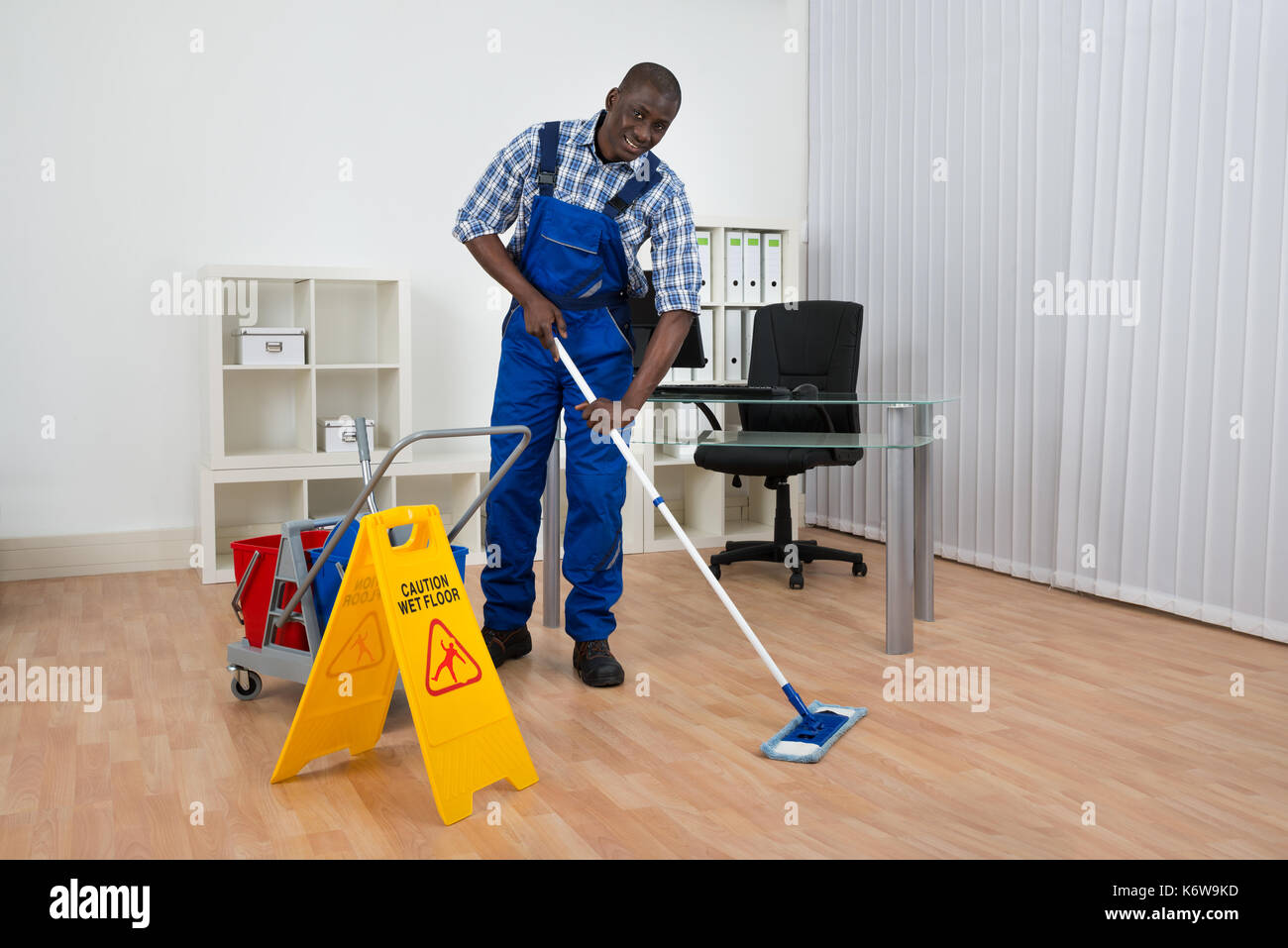 Young Happy Janitor Cleaning Floor With Wet Floor Sign - Stock Image