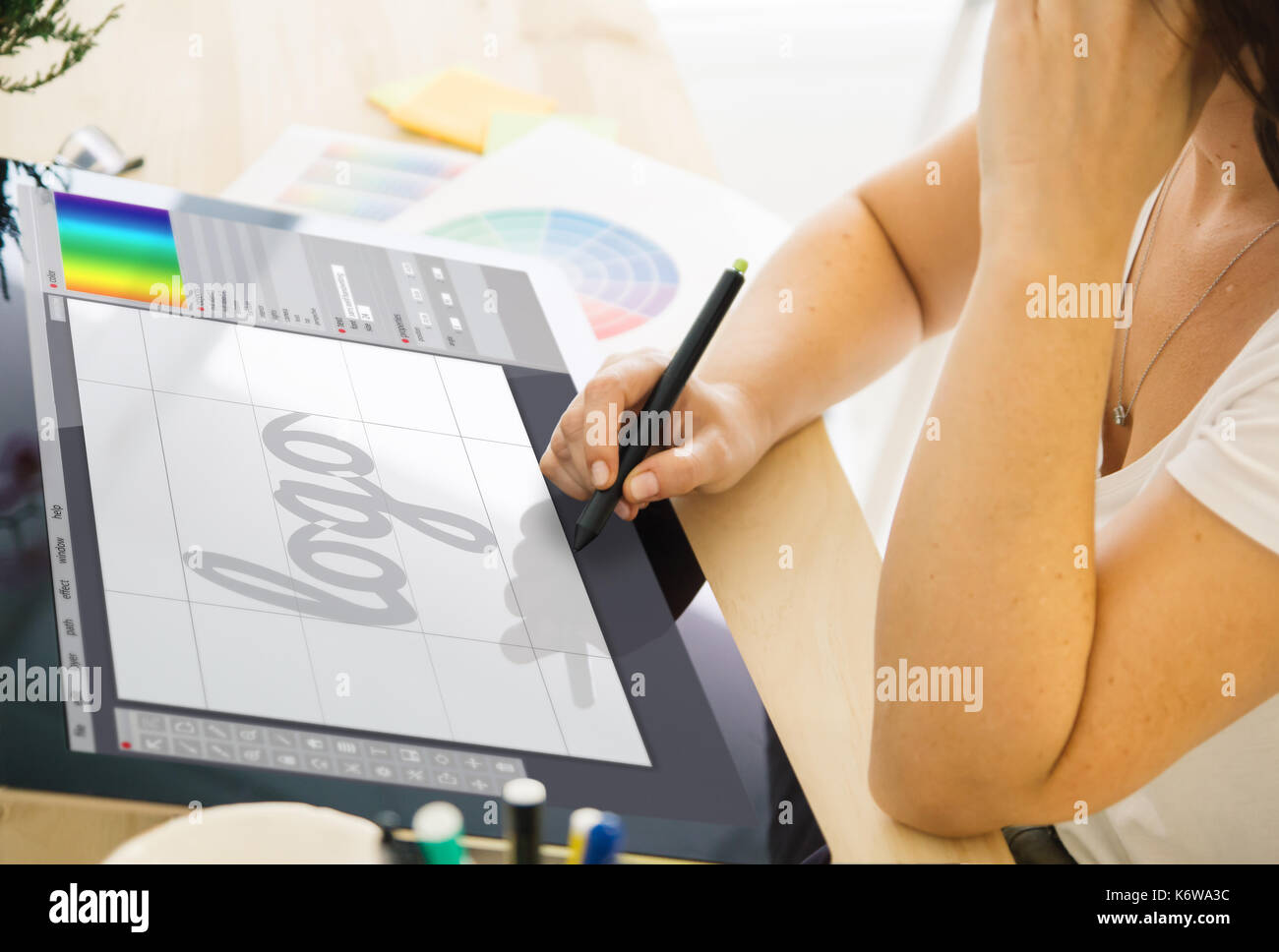 Designer drawing a logo on a tablet. All screen graphics are made up. - Stock Image