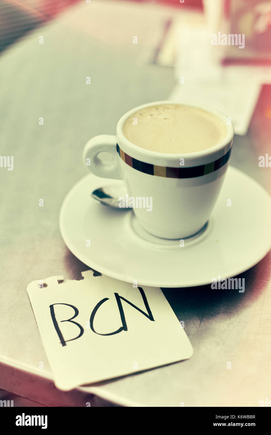 closeup of a cup of coffee and a note with the word BCN, for Barcelona, written in it, on a table in the terrace of a cafe in Barcelona, Spain, with a - Stock Image