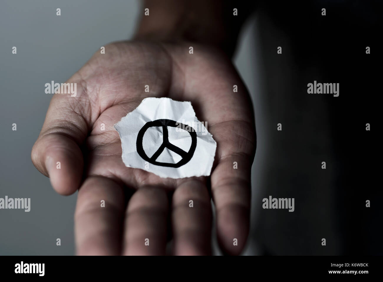 closeup of a young man with a piece of paper with a peace symbol drawn in it, in the palm of his hand - Stock Image