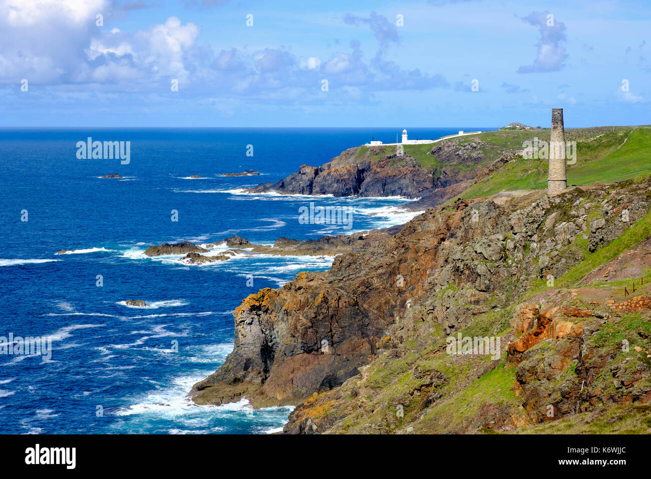 Rocky coast with old chimney from the Levant Mine and Pendeen Lighthouse, St Just in Penwith, Cornwall, England, Great Britain Stock Photo