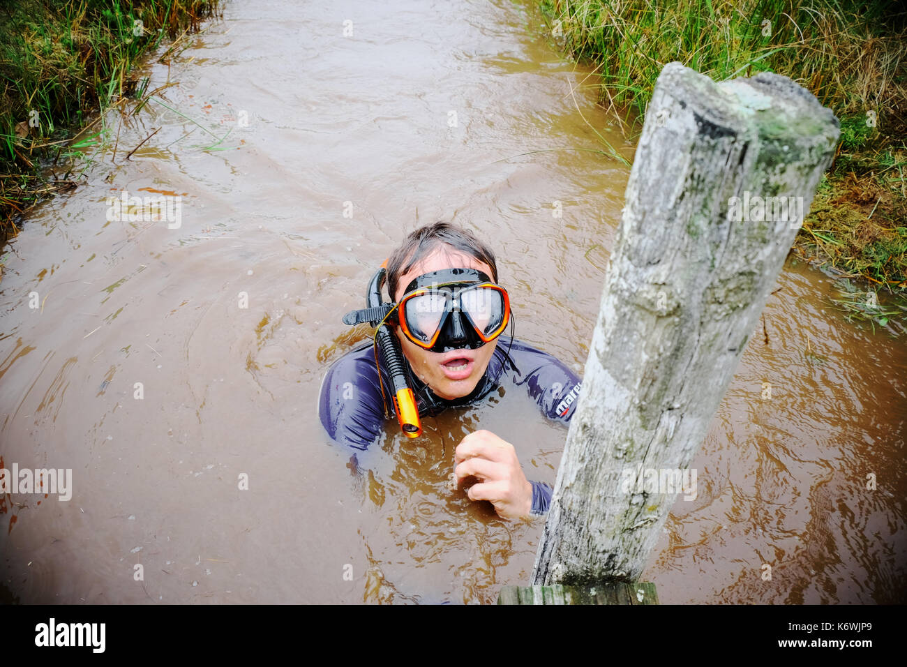 World Bog Snorkelling Championships Wales a cold exhausted competitor reaches the finish post - Stock Image