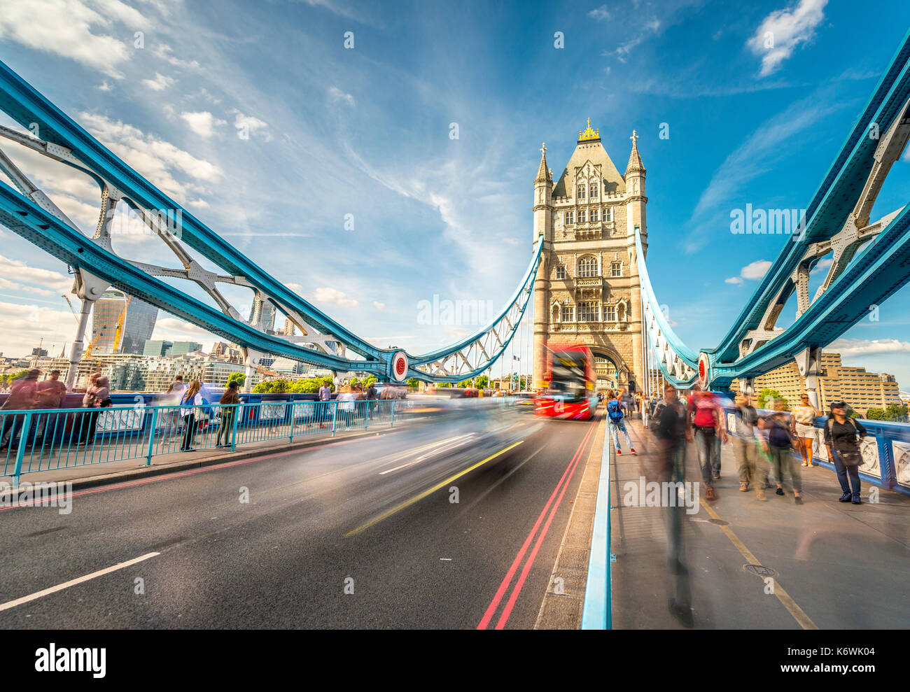 Red double-decker bus on the Tower Bridge with passers-by, motion blur, Southwark, London, England, Great Britain - Stock Image