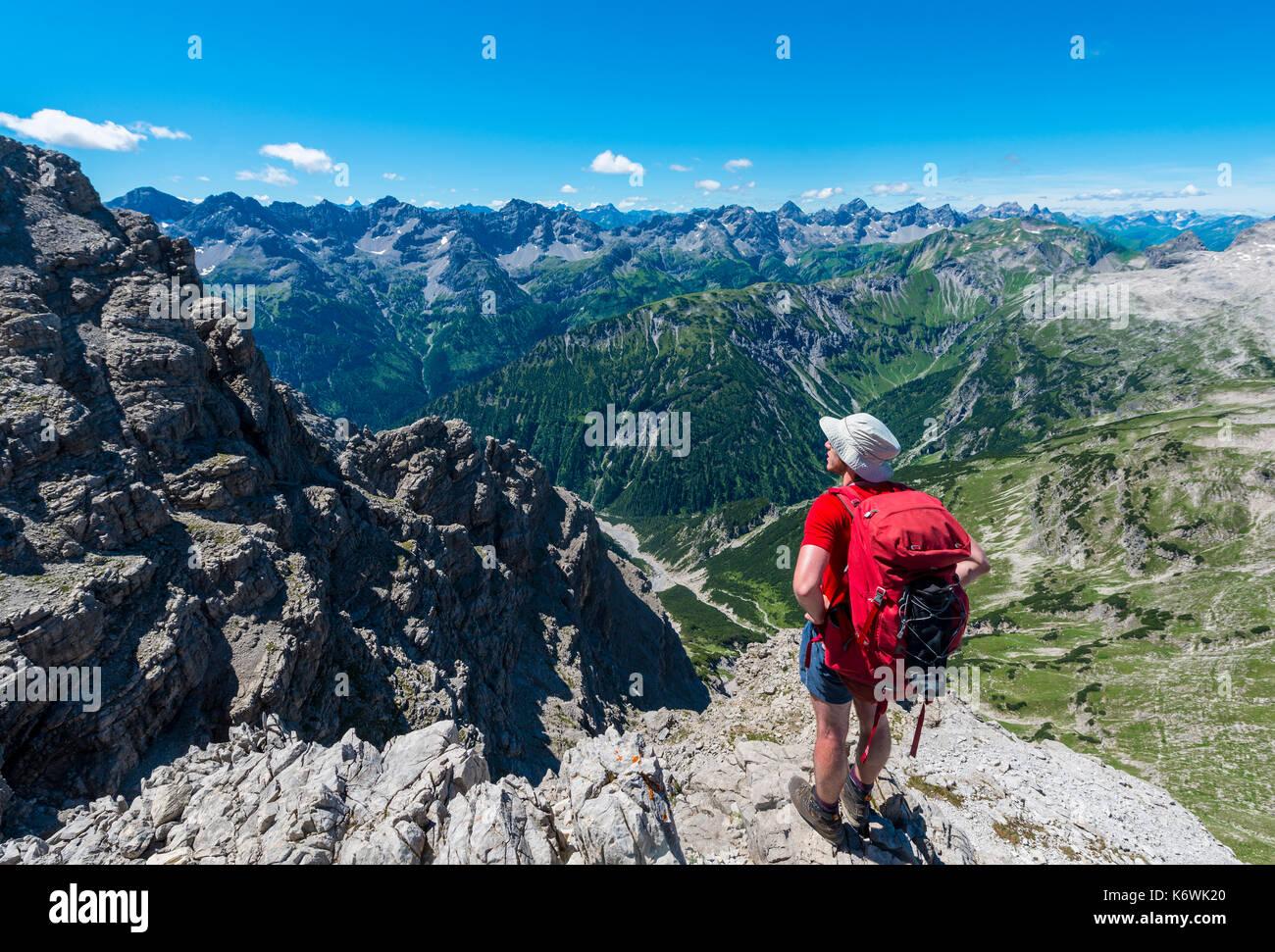 Walker overlooks mountains and Alps, hiking trail to the Hochvogel, Allgäu, Allgäuer Hochalpen, Bavaria, Germany - Stock Image