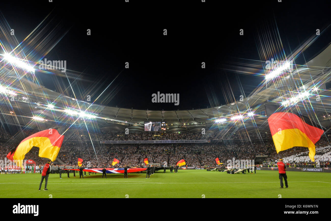 Flag waver with German flags in front of the start of the match, soccer stadium with floodlight in the evening - Stock Image