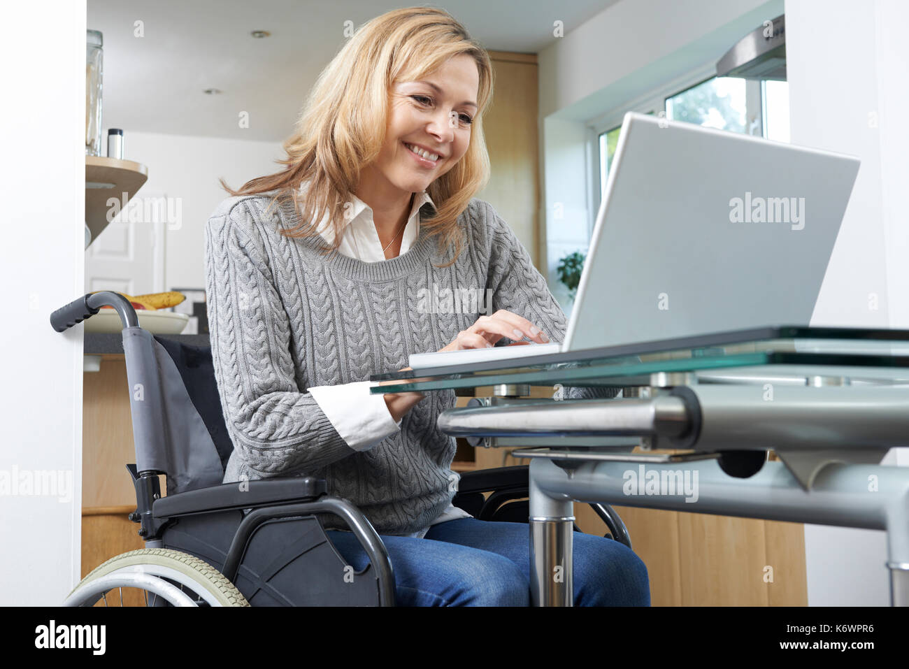 Disabled Woman In Wheelchair Using Laptop At Home - Stock Image