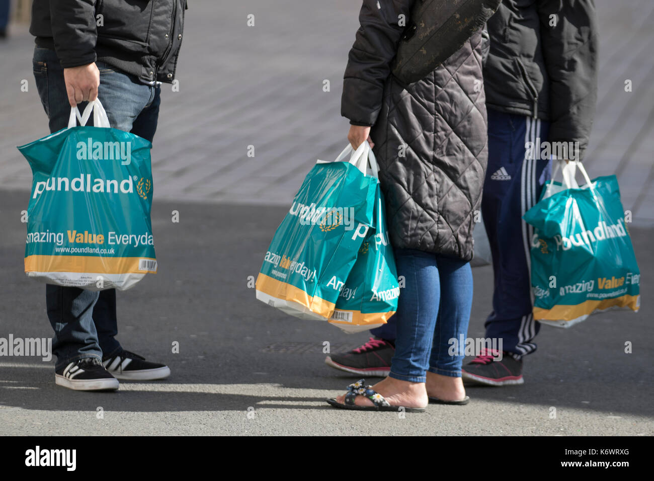 Shoppers with bafs from the Discount retail chain Poundland selling groceries, toiletries, cleaning products and more, all for £1. Blackpool, UK - Stock Image