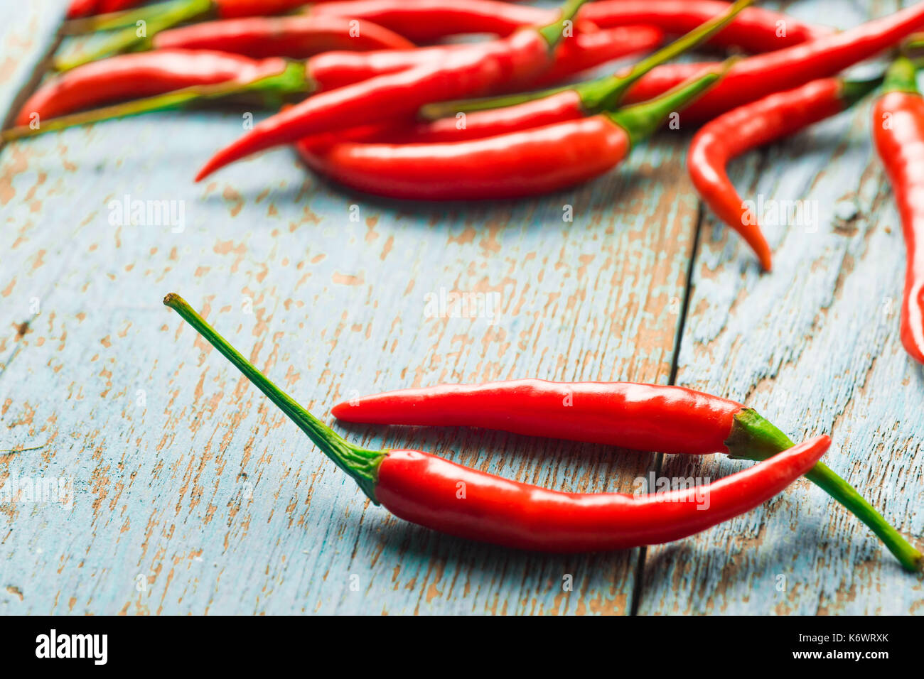 Hot red chili pepper  on a old blue color wooden table with place copy space for text. - Stock Image
