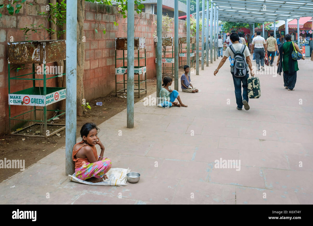 Disabled and disfigured children seeking alms outside a metro station as disembarked passengers walk past in Delhi, India. - Stock Image