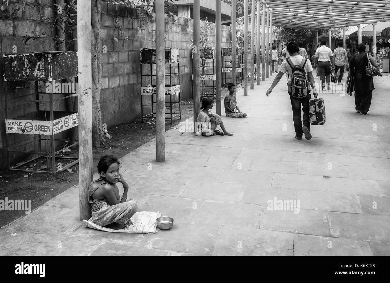 Disabled children seeking alms outside a metro station as disembarked passengers walk past in Delhi, India. - Stock Image