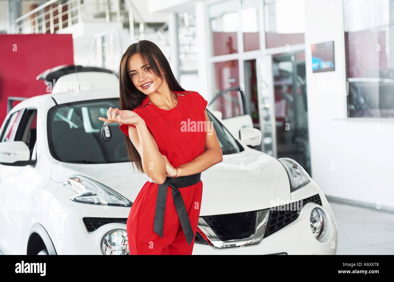 Smiling car salesman handing over your new car keys, dealership and sales concept. Happy girl the buyer. - Stock Image
