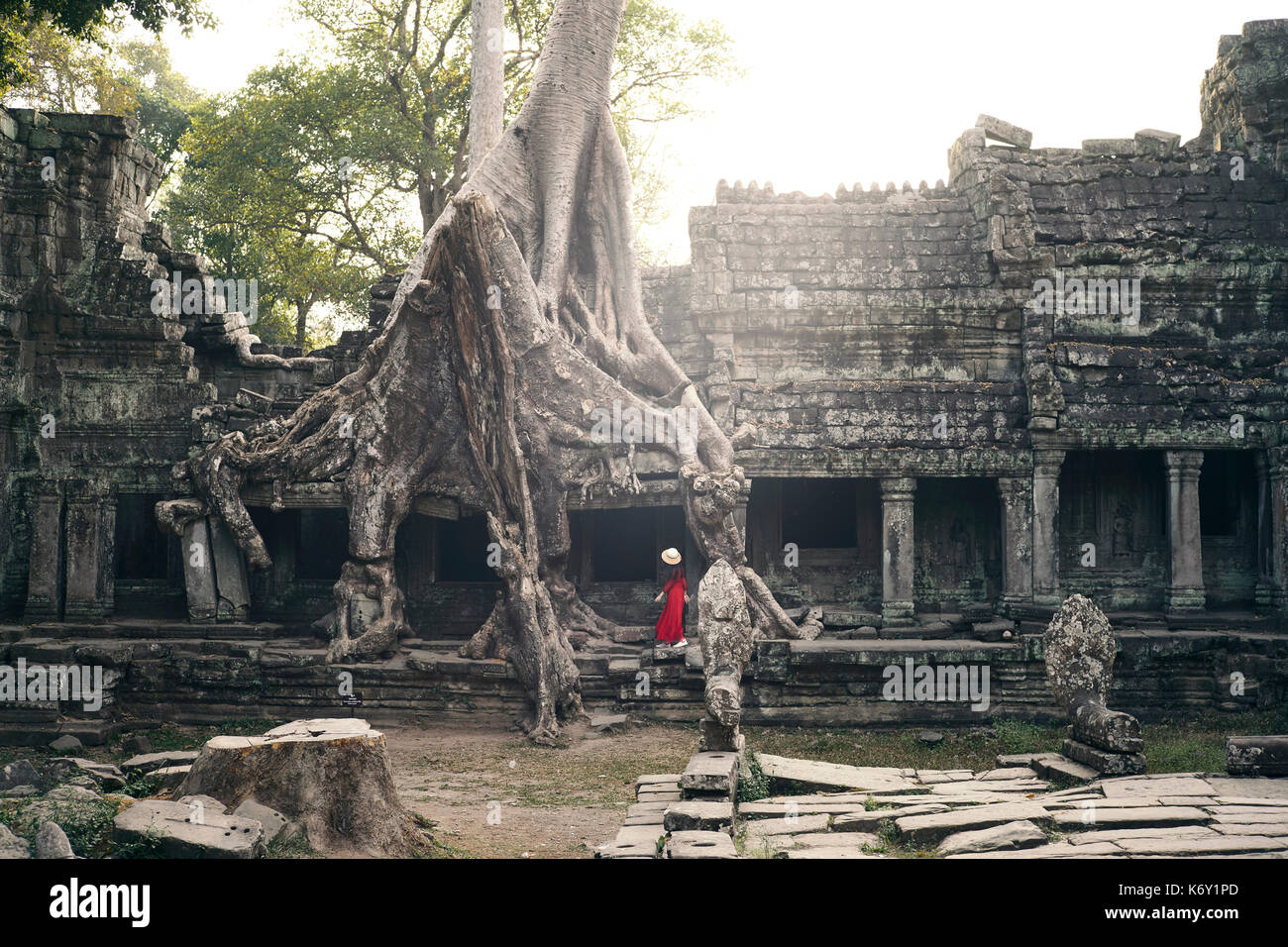 Girl with hat with a red dress walking around the temple of Preah Kahn in Angkor, Siem Reap, Cambodia - Stock Image