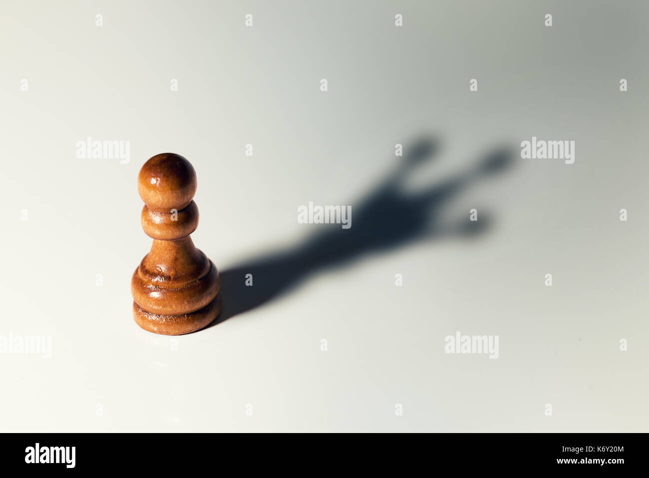 trust yourself concept - chess pawn with king shadow - Stock Image