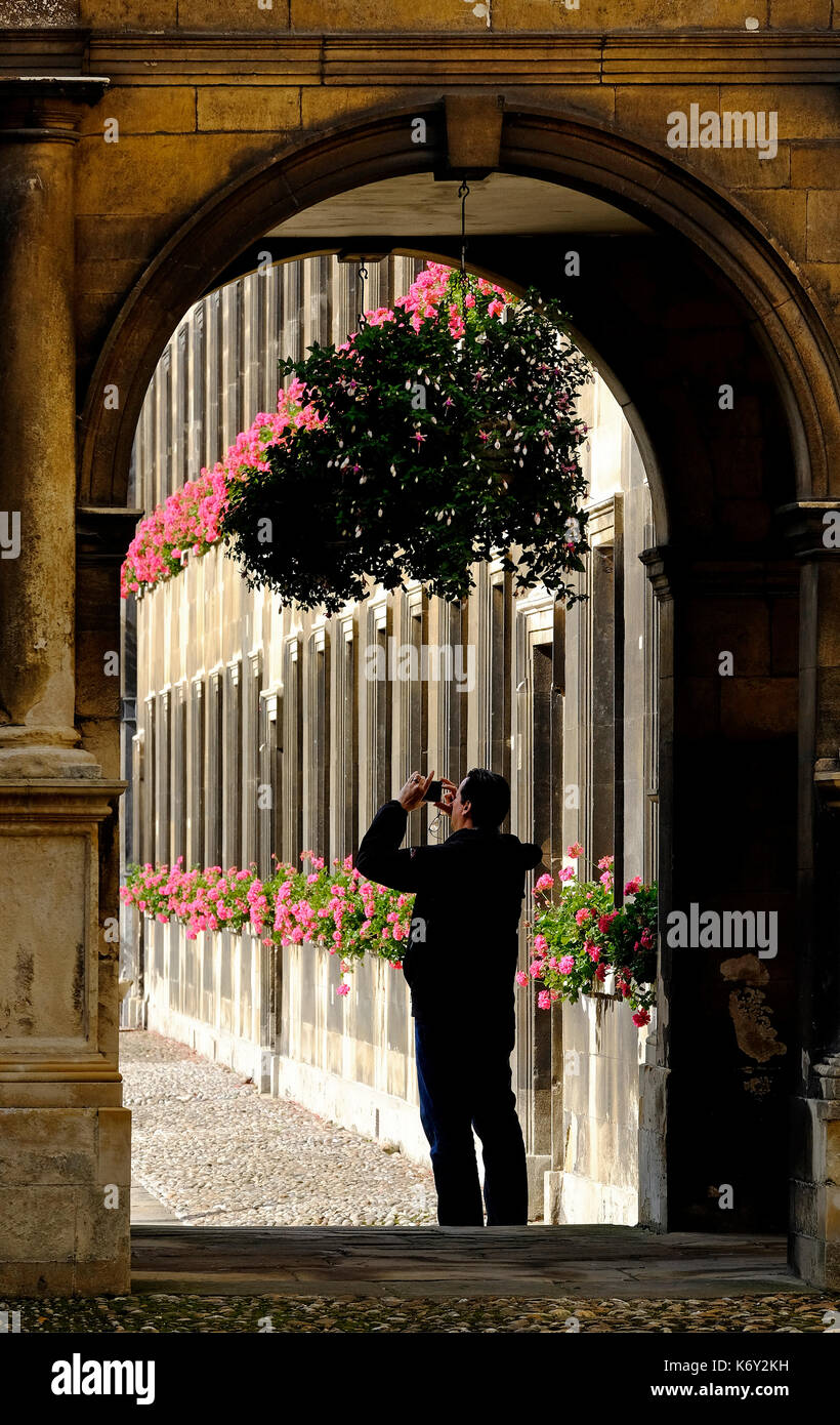 male tourist taking photograph in peterhouse college grounds, cambridge, england - Stock Image