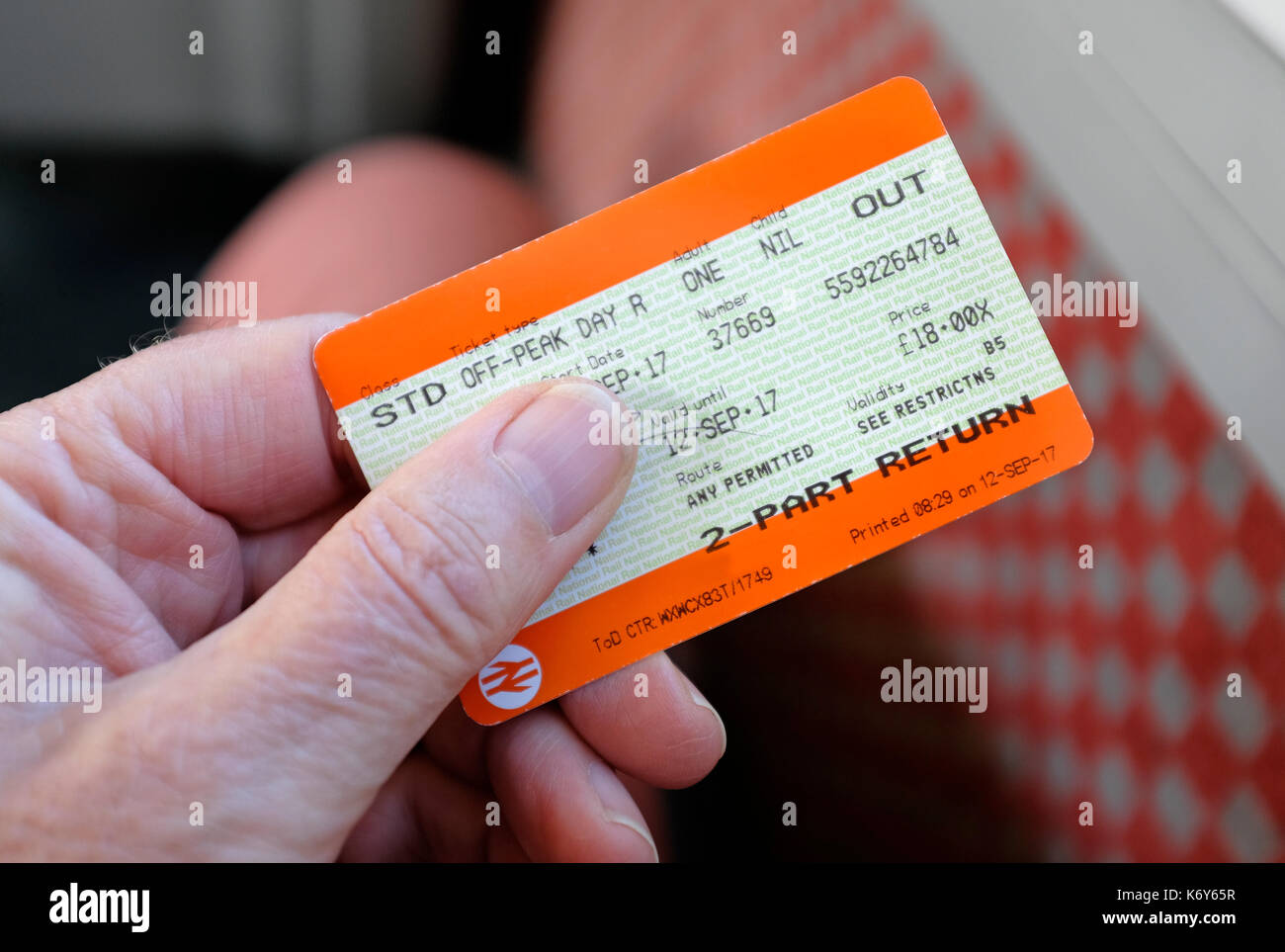 male hand holding rail travel ticket - Stock Image