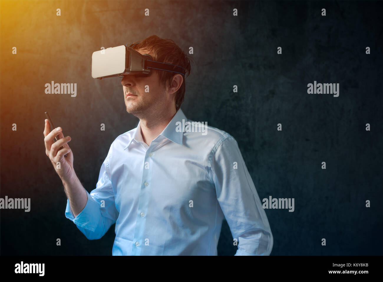 Businessman with VR goggles headset exploring virtual reality immersive technology content - Stock Image