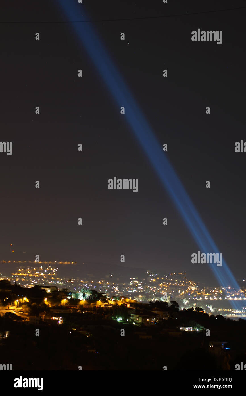 NICE - JULY 14, 2017 :  France commemorates Bastille Day attack in Nice. The city lit up 86 waterfront lights into the night sky towards the Stars. - Stock Image