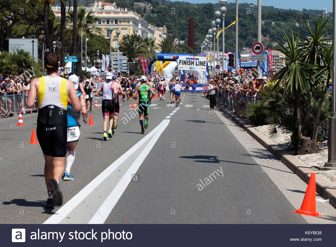 Competitors head towards the finish line after running a full marathon as part of the Nice Ironman Triathlon - Stock Image
