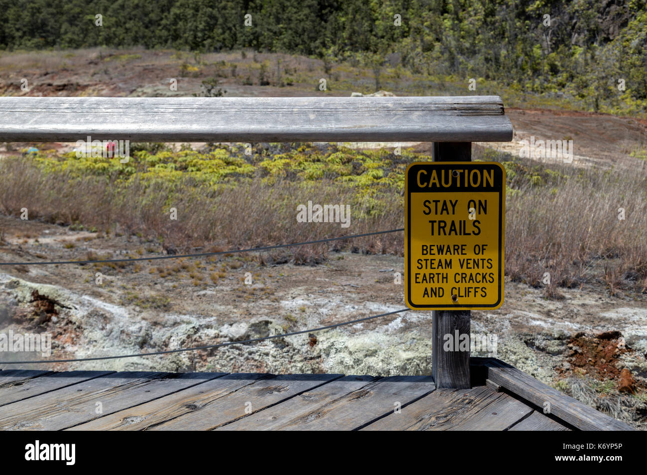 Warning sign about the danger one can encounter along the Sulphur Banks trail, nailed to an old wooden bench. located in the Volcanoes National Park. - Stock Image