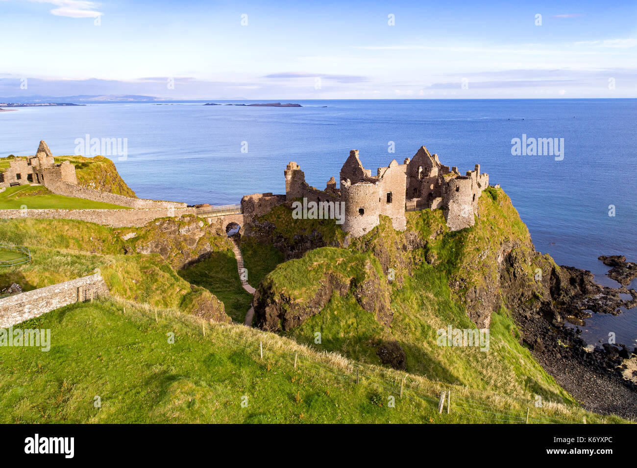 Ruins of medieval Dunluce Castle on a steep cliff. Northern coast of County Antrim, Northern Ireland, UK. Aerial view. - Stock Image