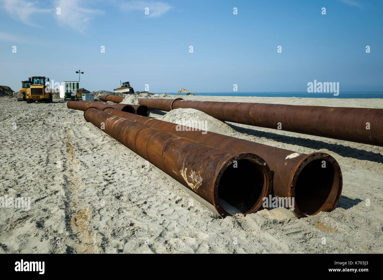 Am Strand, Langeoog.  Deutschland.  Germany.  A close-up of the industrial pipeline used as part of the active beach rebuilding, Strandaufschüttung, pumping sand up onto the sandy beaches.  Diggers and industrial machinery used to lay the pipeline along the beaches.  The metal pipes, which are heavily corroded with rust, create leading lines to the industrial machinery.  It's a sunny day with only light clouds in the sky. - Stock Image