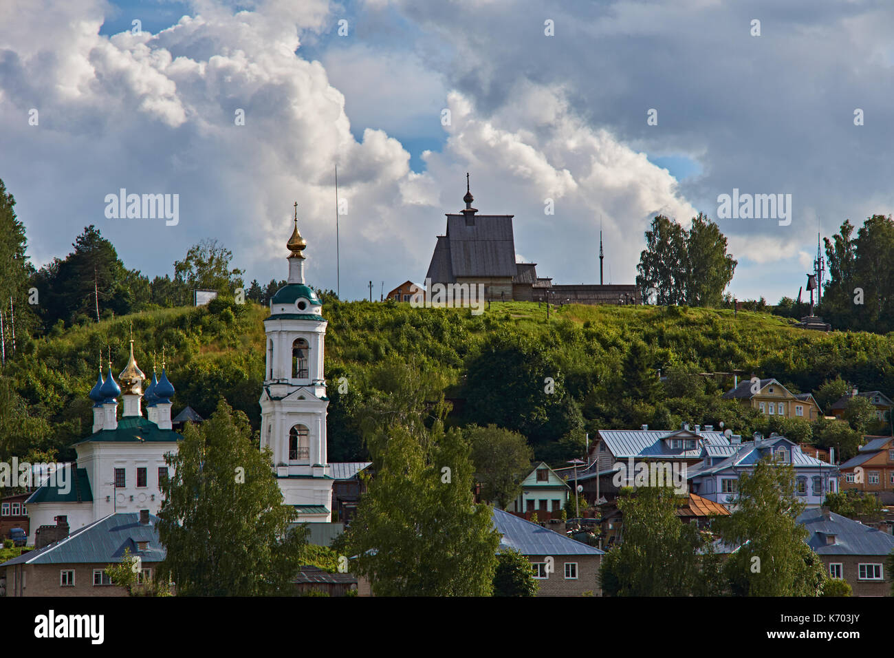 A white Orthodox church with a bell tower stands on a hill. Above it is a wooden one. Plyos, the Golden ring of Russia.Stone and wooden temples - Stock Image