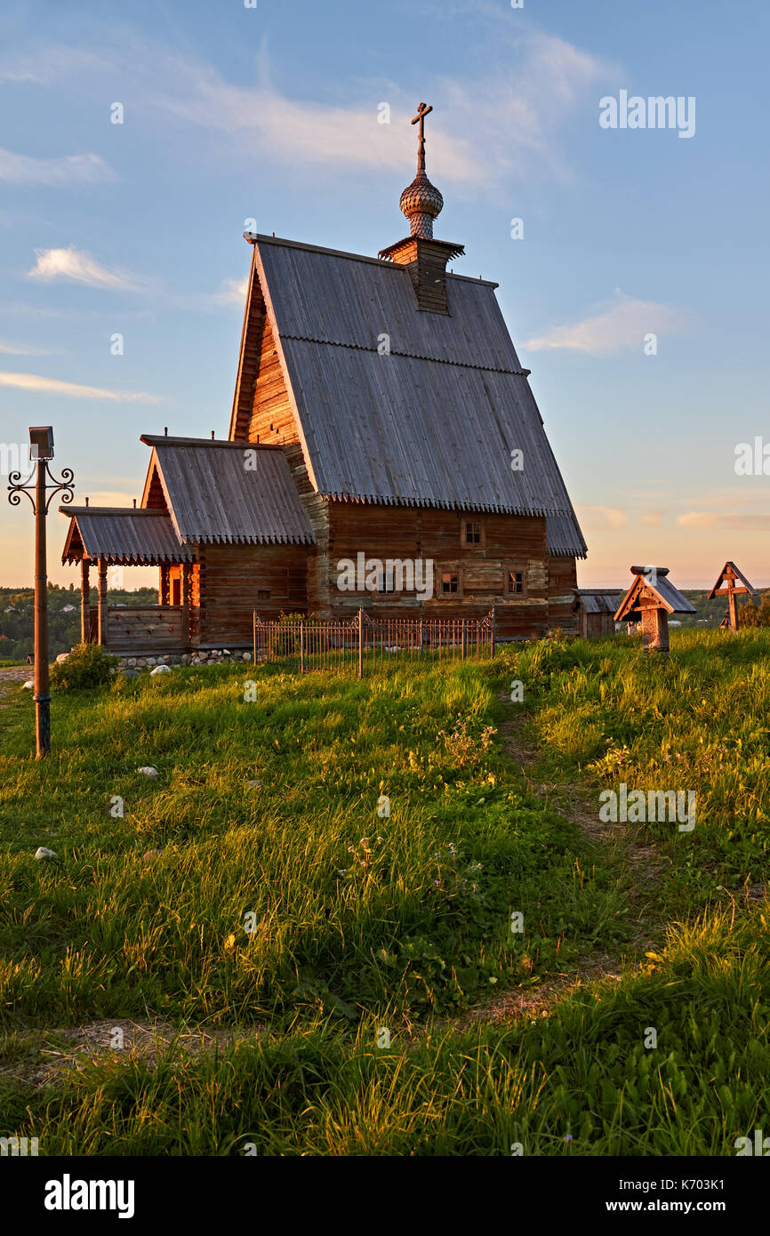 A wooden orthodox church stands on a hill.The church is illuminated by the rays of the sun,which goes beyond the horizon.Plyos,the Golden ring of Russ - Stock Image