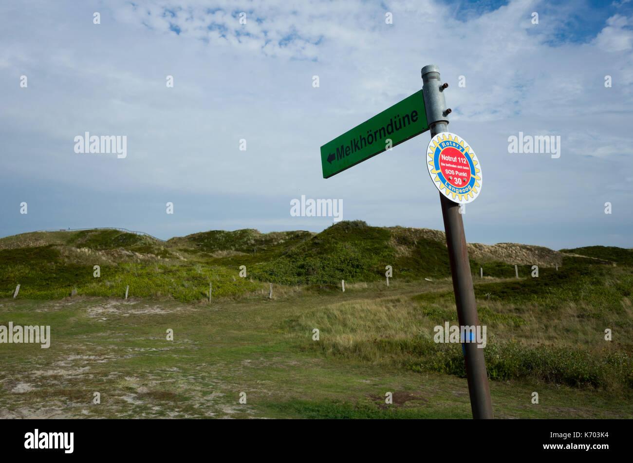 Melkhörndüne, Langeoog.  Deutschland.  Germany.  A signpost directing tourists towards the Melkhörndüne sand dunes attraction.  It's a bright hazy day with light cloud cover. - Stock Image