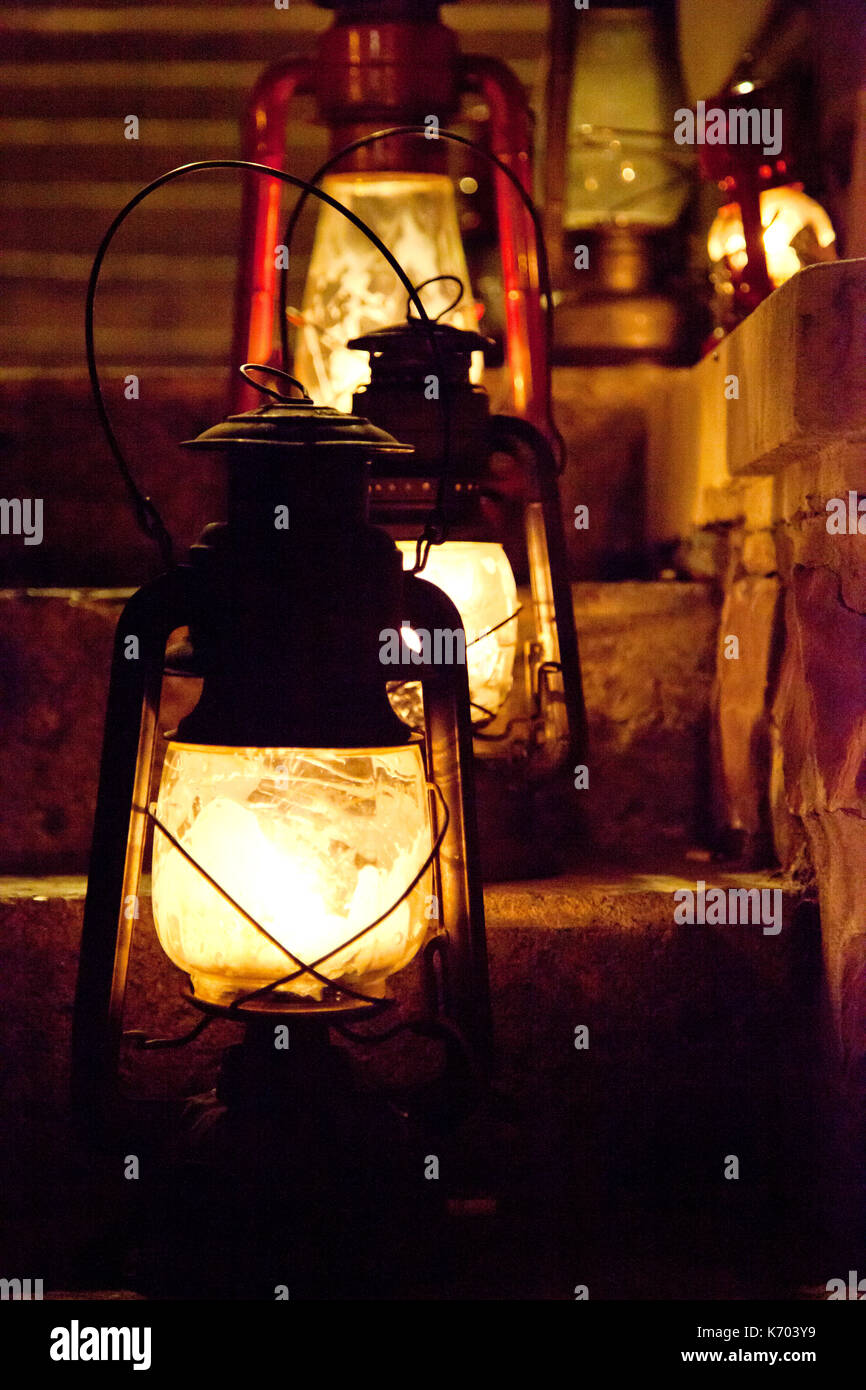 old fashioned oil lamps or lanterns sitting on a flight of stairs at night - Stock Image