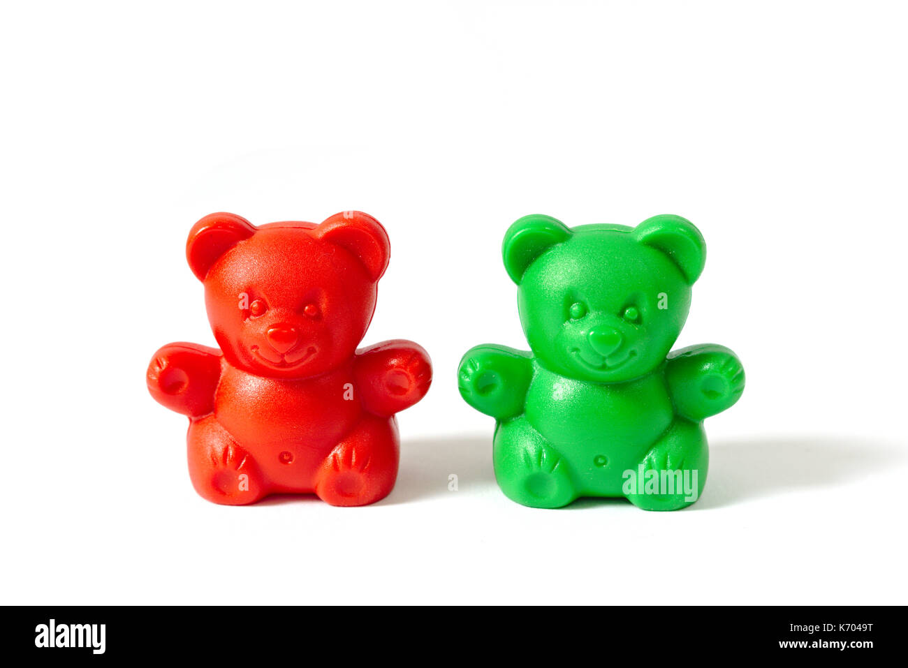 Small red and green plastic toy bears isolated on white background - Stock Image