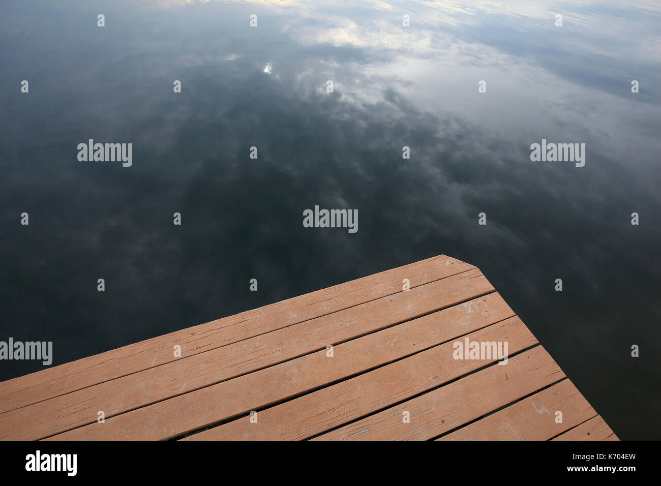 lake dock with sky reflecting in water - Stock Image