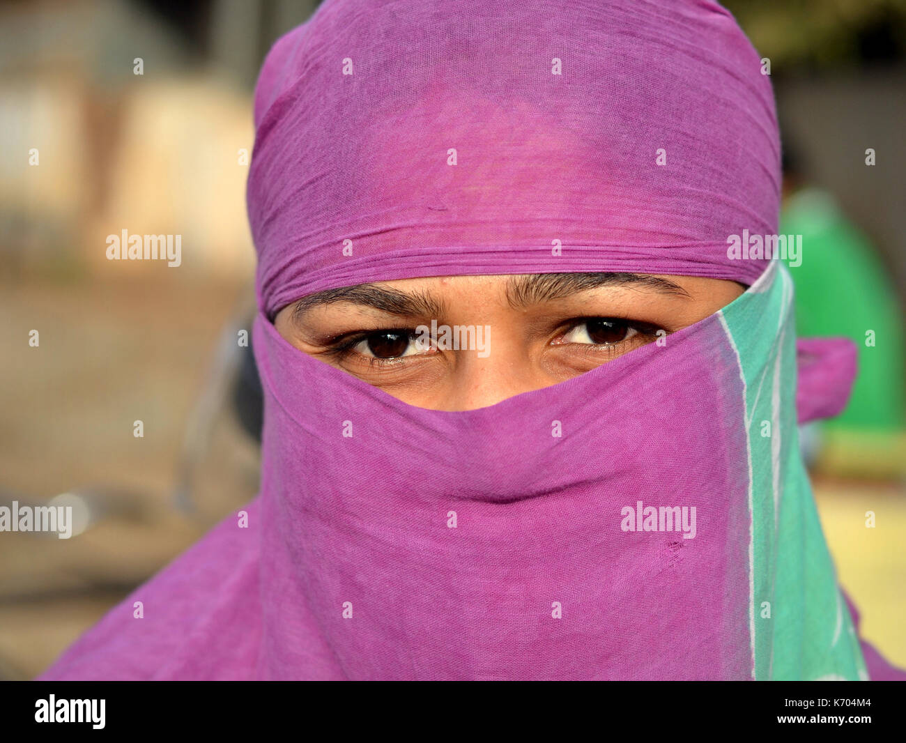 Young Indian woman with scrutinizing eyes, covering her hair and face with a trendy secular headscarf; Jagdalpur, - Stock Image