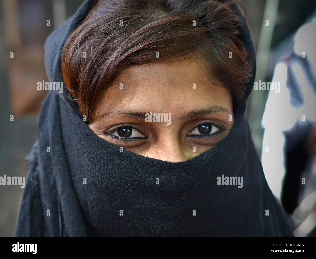 Young Indian Muslimah with smiling eyes and casual black niqab; Ahmedabad, Gujarat, Western India - Stock Image