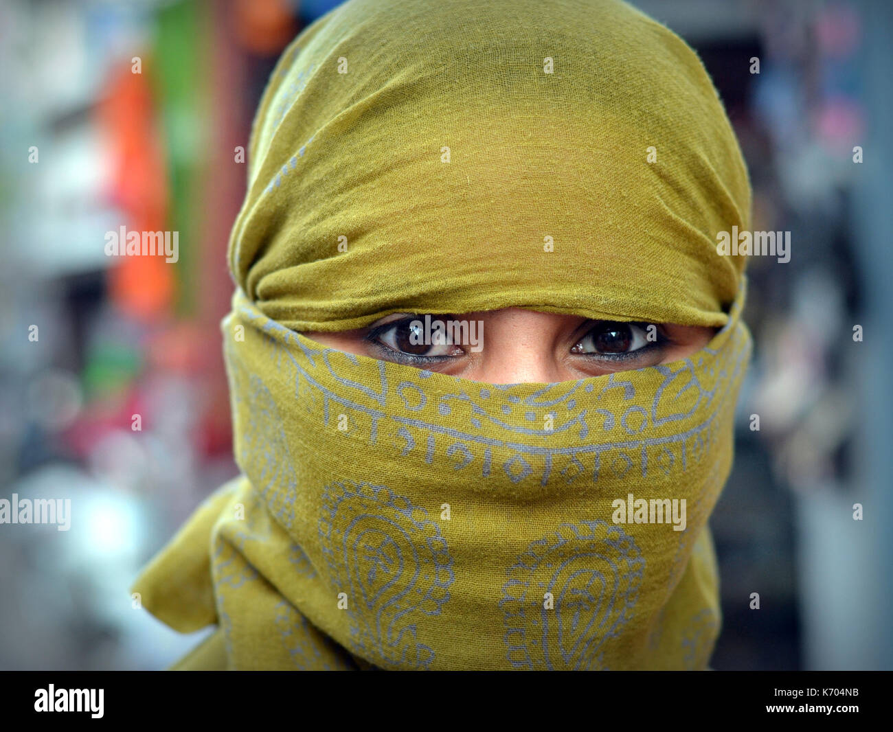 Young Indian woman with beautiful eyes, covering her hair and face with a trendy secular, yellow headscarf; Bhuj, - Stock Image