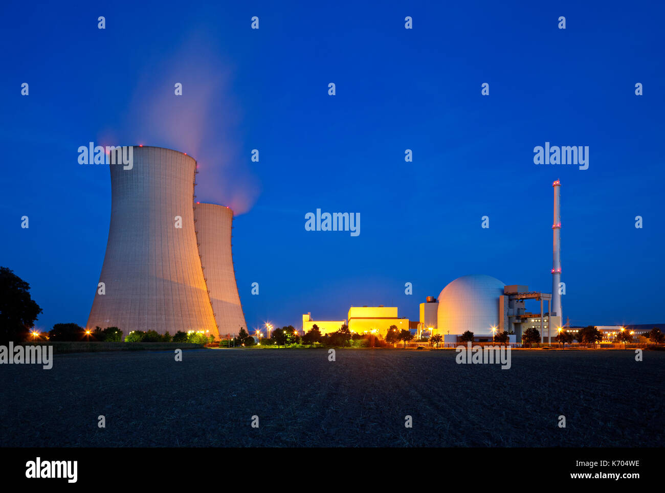 A nuclear power plant with night blue sky. - Stock Image