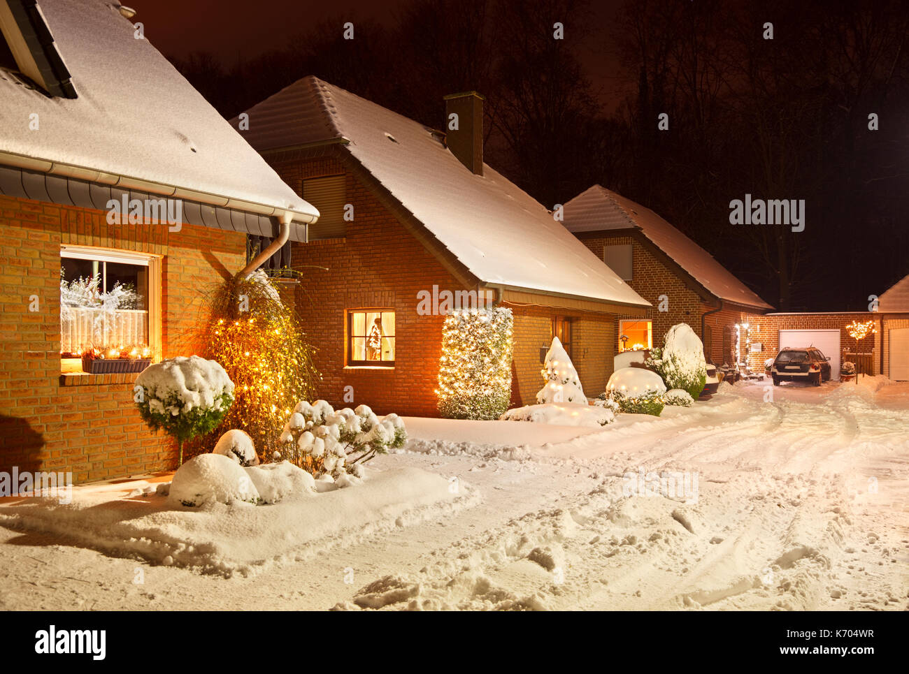 Night shot of a little village street after a snow fall during christmas time. - Stock Image