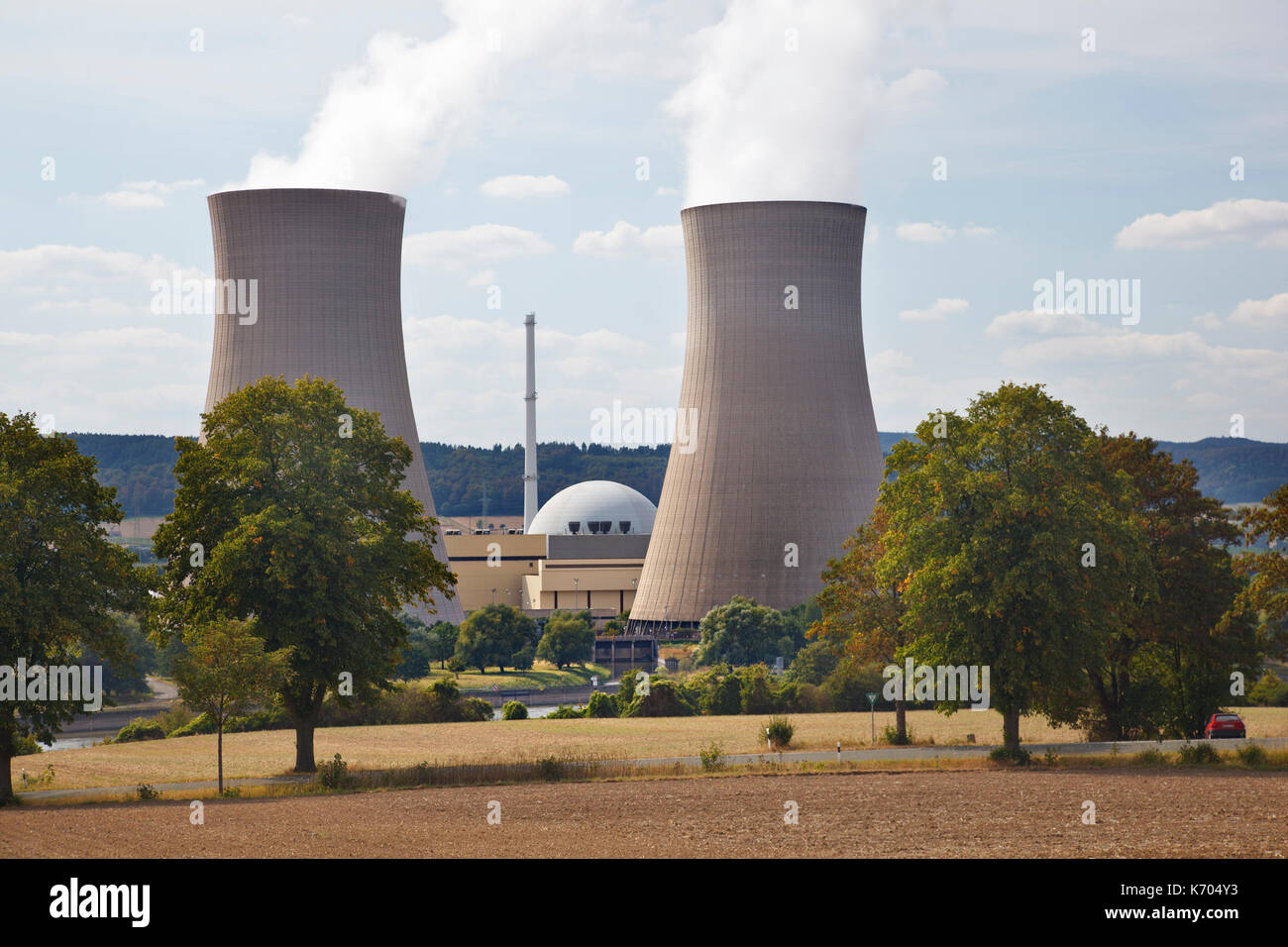 Two tall cooling towers and the reactor building of a nuclear power station in green river landscape seen from a hill. - Stock Image