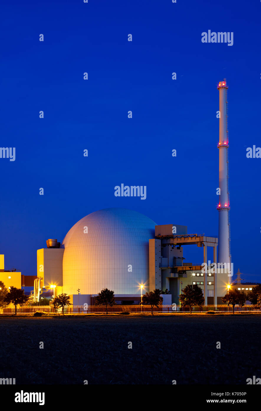 Reactor building of a large nuclear power plant with night blue sky. - Stock Image