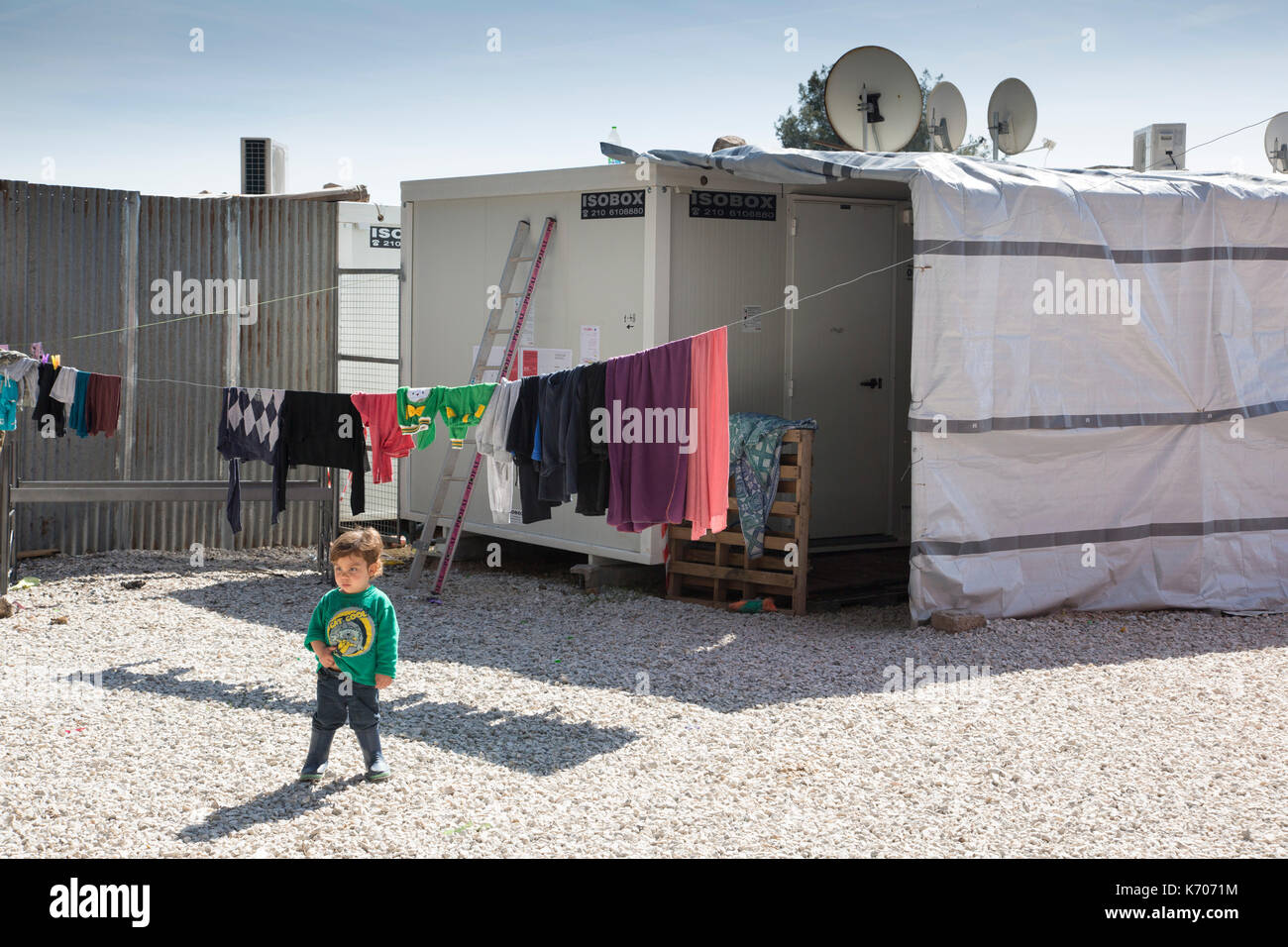 On the gravel between prefabricated units housing refugees from Syria, a lone child surveys Ritsona Refugee Camp. - Stock Image