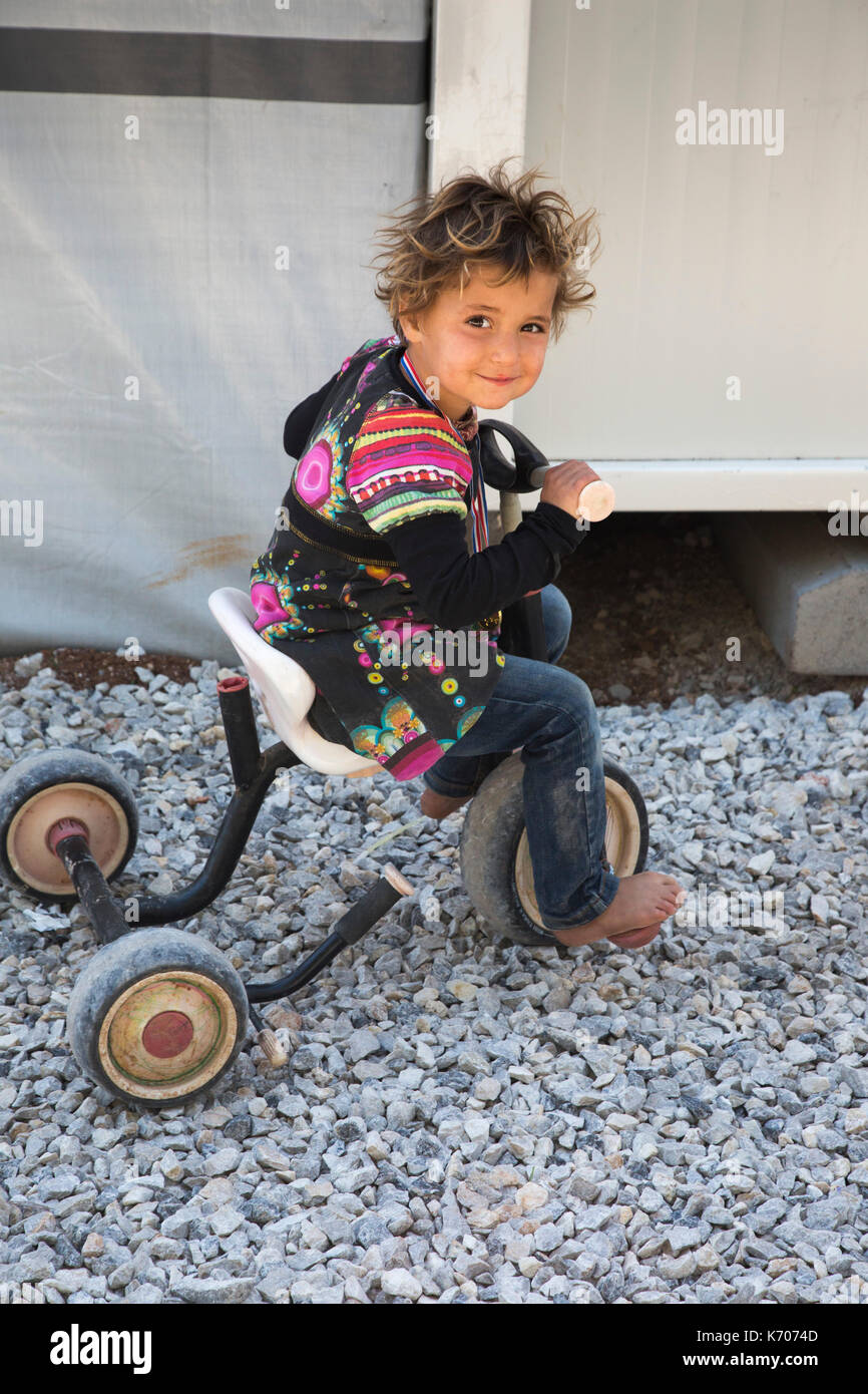 Smiling at the camera, a child refugee from Syria atempts to ride a tricycle on the stony ground of the Ritsona Refugee Camp. - Stock Image