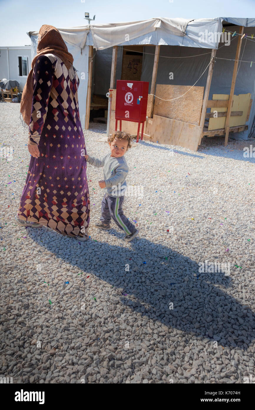 As they walk past rows of emergency homes, a boy holds on to his mother's dress. She walks on as he is distracted and looks in other directions. - Stock Image