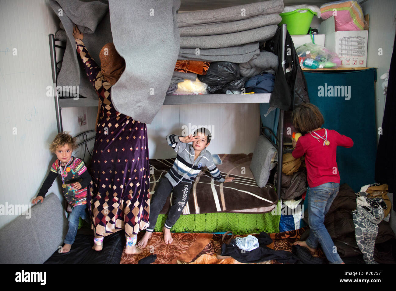 A Syrian refugee mother, tidies her prefabricated  'Isobox' house by stacking the mattresses on top of some of their possessions on the upper bunk . - Stock Image