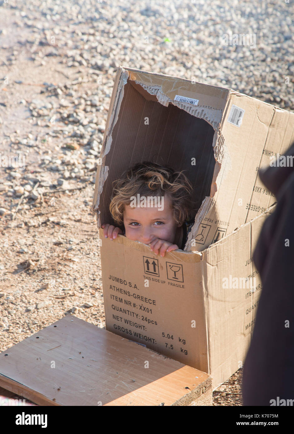 A child plays happily, hiding in a cardboard box on the bleak stony ground of the Ritsona Refugee Camp in Greece. - Stock Image