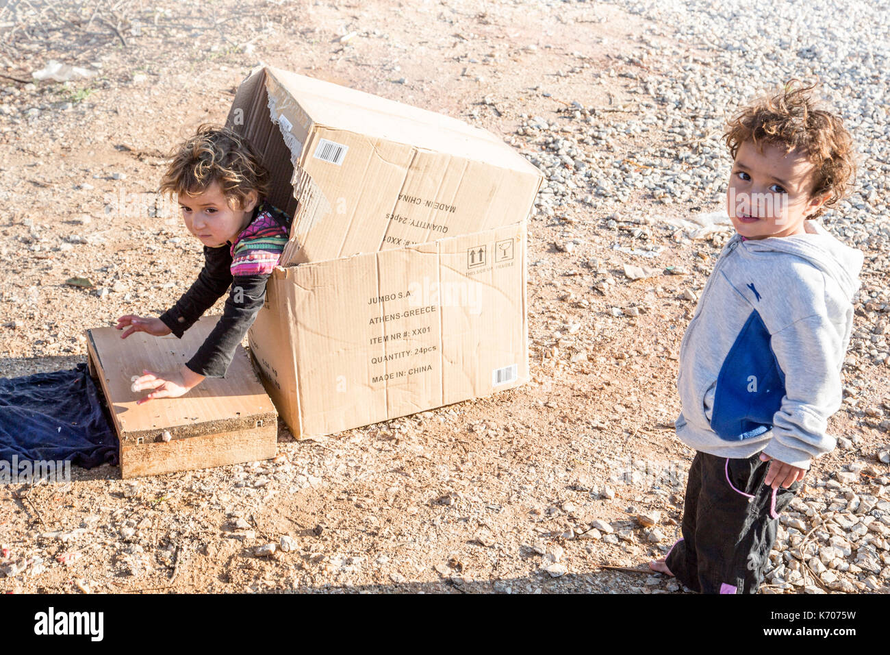 A child plays happily in a cardboard box on the bleak stony ground of the Ritsona Refugee Camp in Greece as his friend looks at the camera. - Stock Image