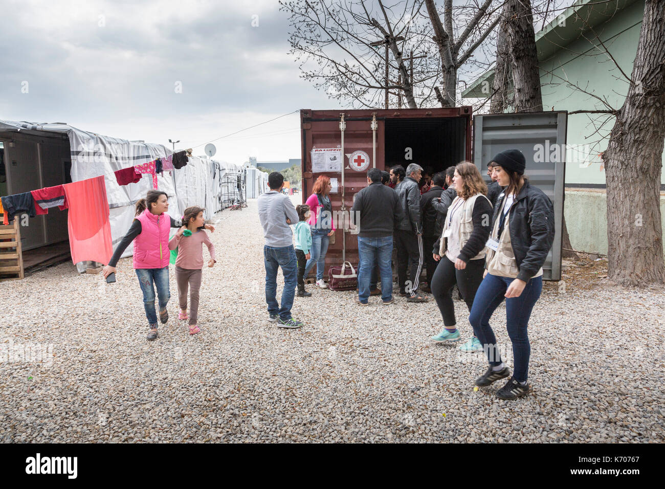 At the Ritsona Refugee Camp in Greece, men gather by a shipping container, used as office and distribution centre by the Hellenic Red Cross. - Stock Image