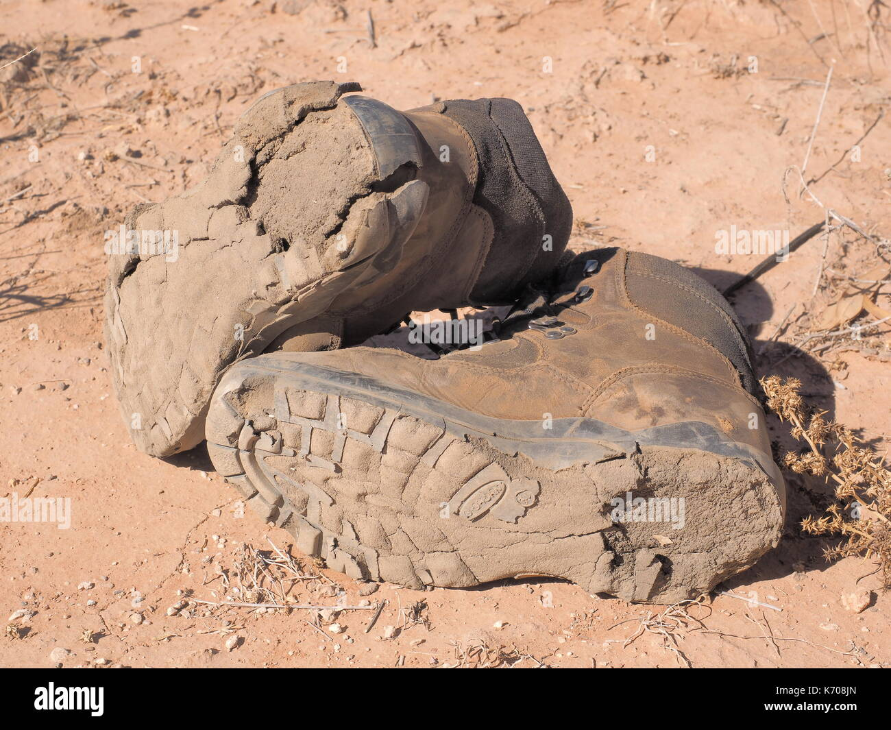 Pair of hiking boots with completely destroyed soles at MacDonnell ranges near Alice Springs, Northern Territory, Australia 2017 - Stock Image