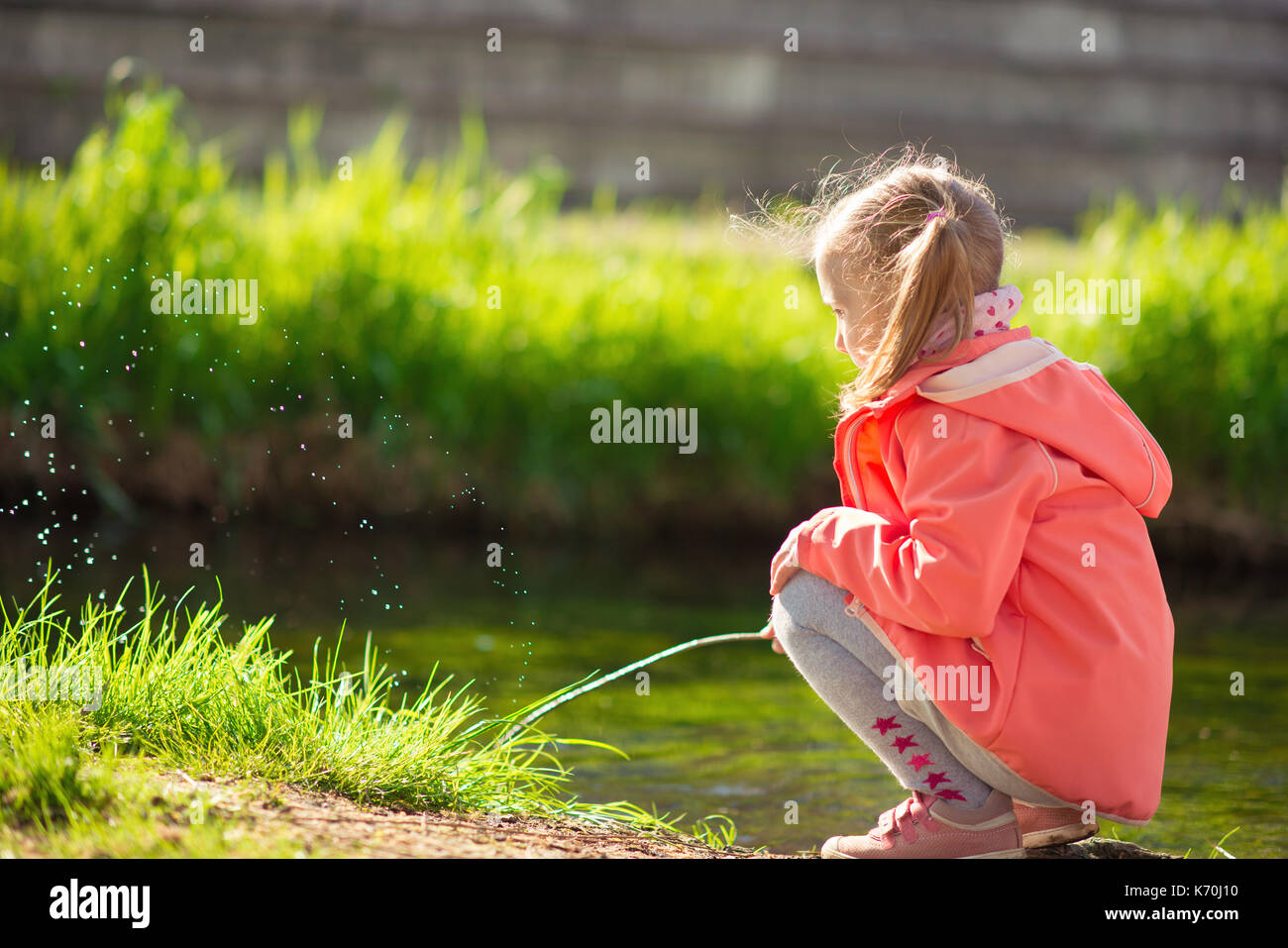 Happy adorable little blonde girl playing near pond in sunny day - Stock Image