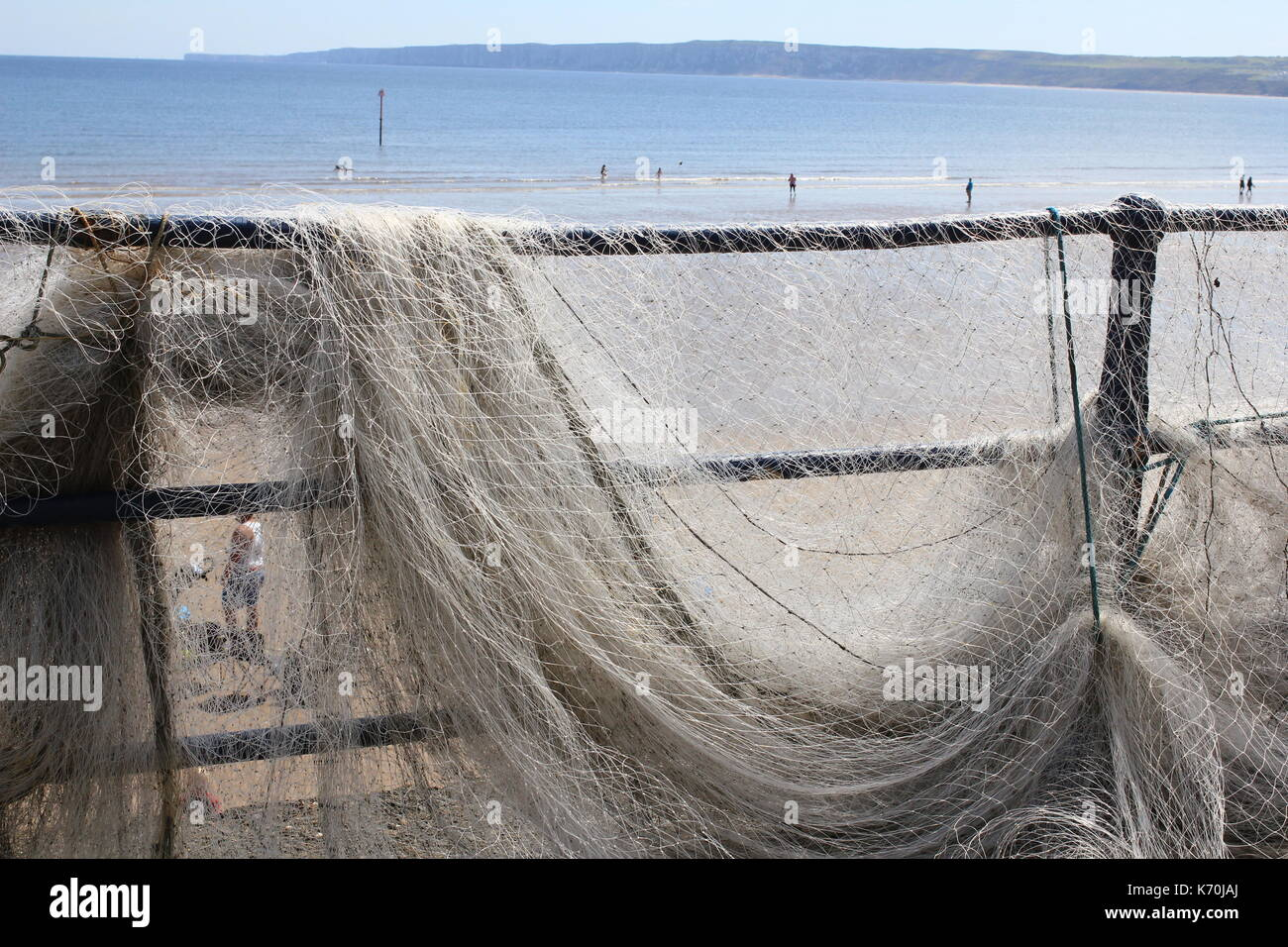 Fishing net drying on the seafront - Stock Image