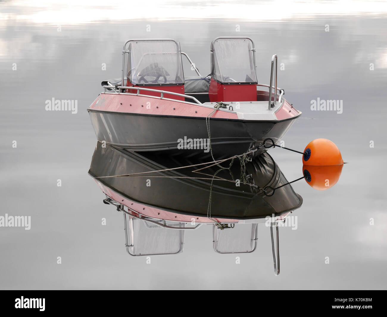 Buster aluminium boat reflects in the calm lake Åresjön, Åre, Jämtland, Sweden.Orange buoy secures the boat. - Stock Image